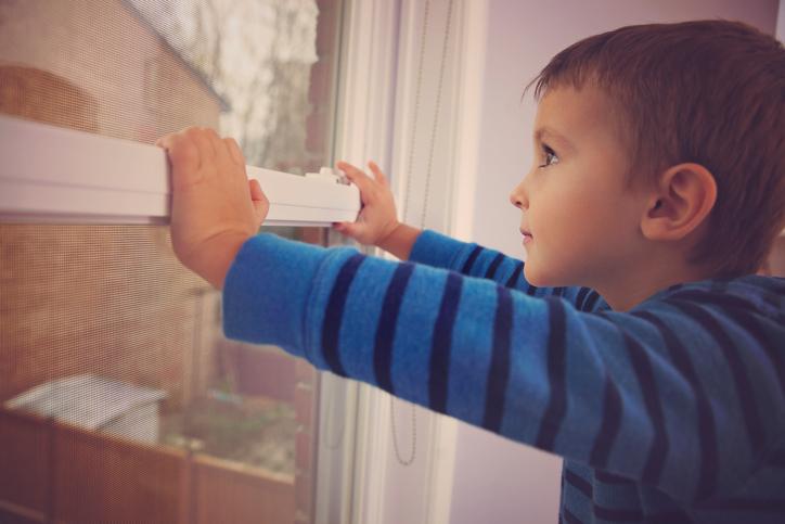 Niño viendo hacia afuera desde una ventana.
