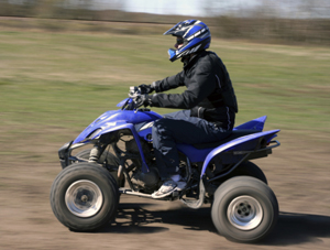 Man wearing a helmet riding an ATV on dirt