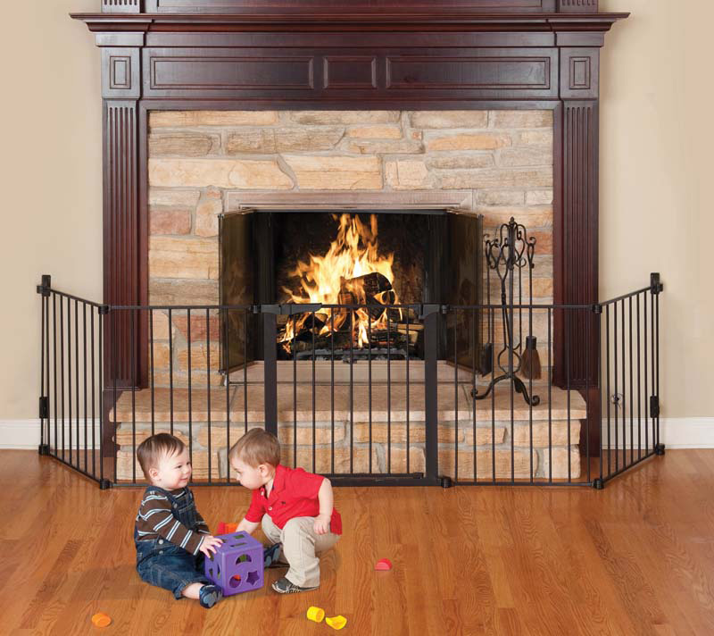 Two young children playing in front of a screened off fireplace