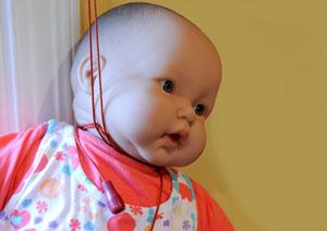 Muñeca siendo estrangulada por un cordón de ventana.