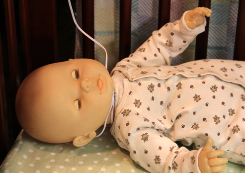 Baby doll in a crib with a baby monitor cord wrapped around its neck