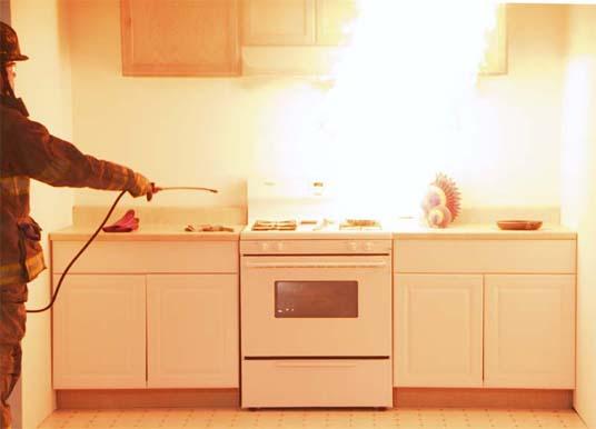 Un bombero riega agua a un sartén en llamas que explota