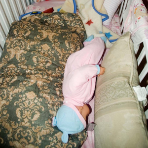 Re-creation of baby doll in crib filled with pillows. Baby is between the two pillows.