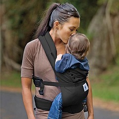 Mother carrying baby in soft infant carrier
