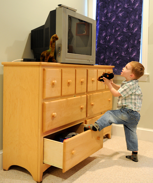 Child Climbing On A Dresser With A Television On Top