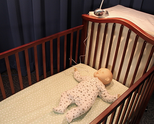 Baby in a crib with a video monitor cord next to the crib