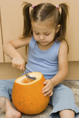 Girl scooping pumpkin with a spoon